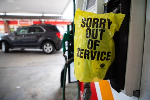 """An """"Out Of Service"""" bag covers a gas pump as cars continue line up for the chance to fill their gas tanks at a Circle K near uptown Charlotte, North Carolina on May 11, 2021 following a ransomware attack that shut down the Colonial Pipeline. - Fears the shutdown of a major fuel pipeline would cause a gasoline shortage led to some panic buying and prompted US regulators on Tuesday to temporarily suspend clean fuel requirements in three eastern states and the nation's capital."""