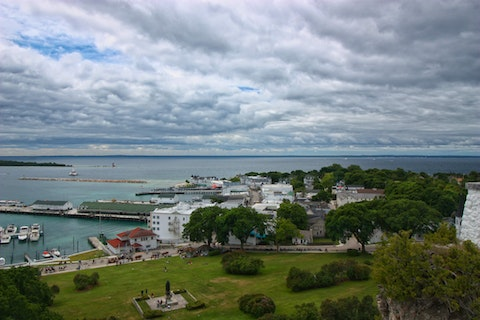 Looking down from Fort Mackinac on Mackinac Island with a view of rolling grassy hill to the port at the Straits of Mackinac between Lake Michigan and Lake Huron.