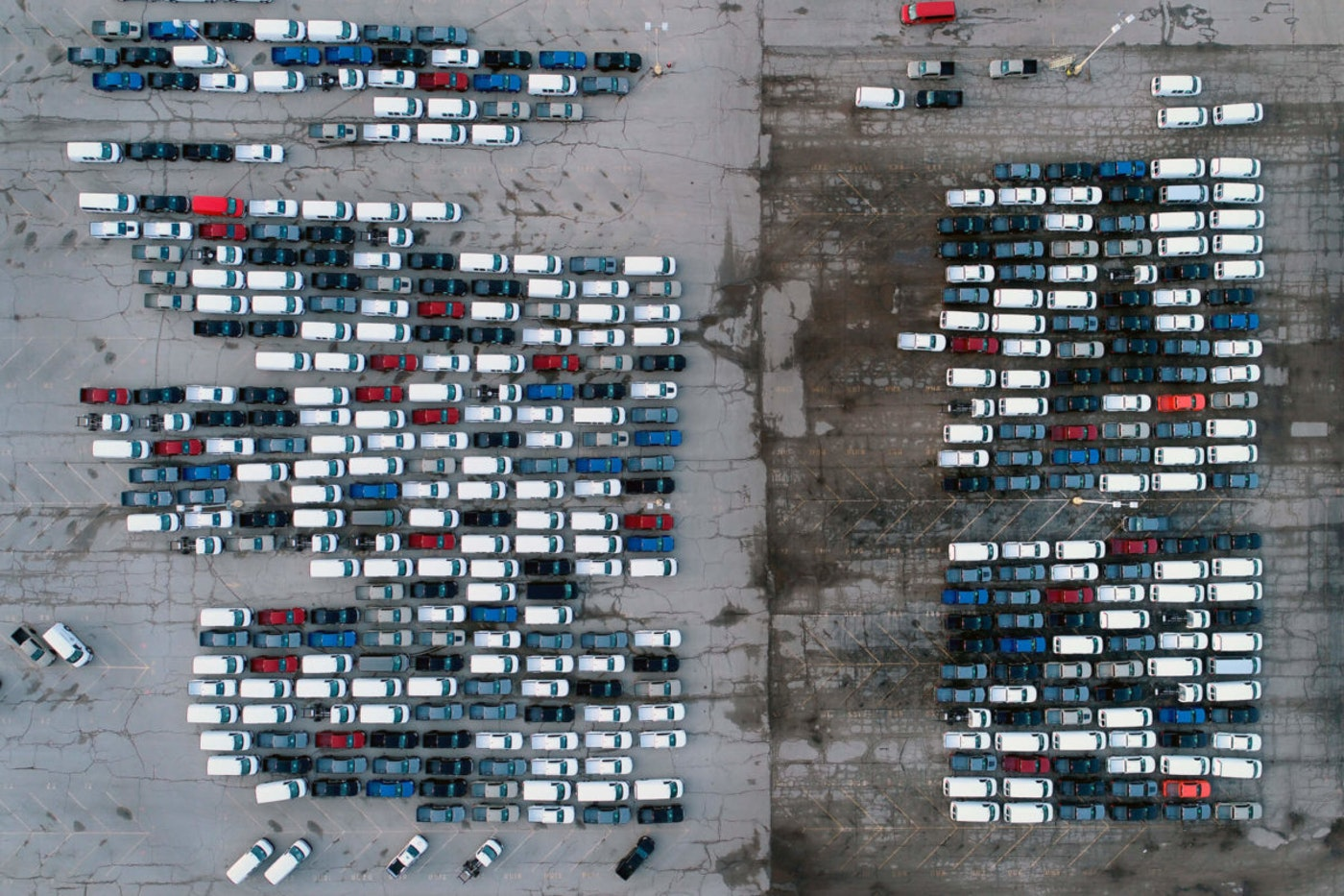 Mid-sized pickup trucks and full-size vans are seen in a parking lot outside a General Motors assembly plant where they are produced in this March 2021 photo. A global shortage of semiconductors has forced General Motors to cut production at some North American factories over the past year. (AP Photo/Jeff Roberson)