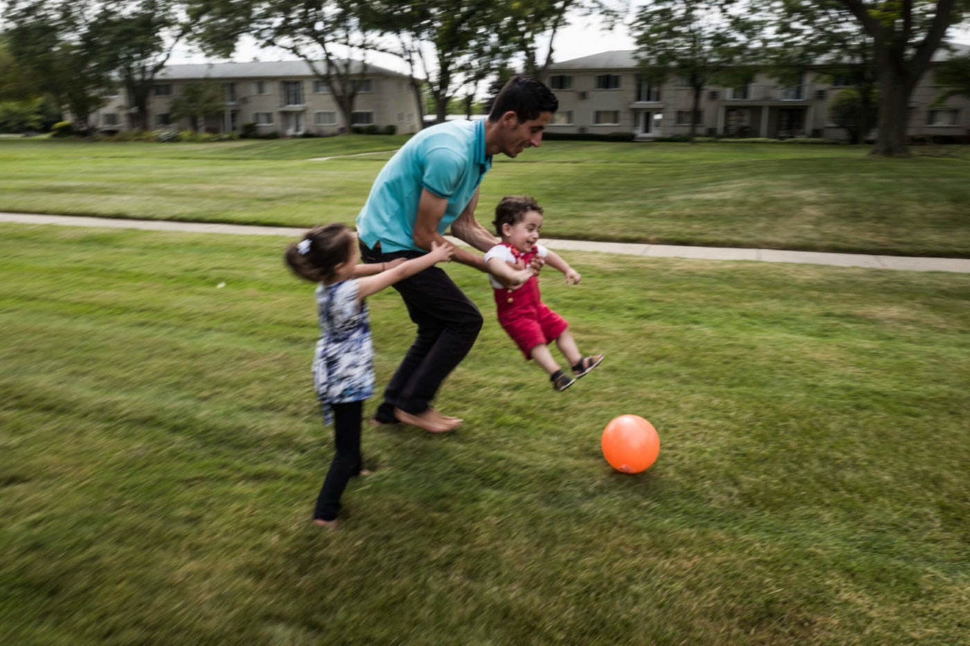 Nedal Al Hayek plays with his son, Taym, and daughter, Layal, outside their new home on July 28, 2015 in Bloomfield Hills, Michigan. The family, including Nedals wife, Raeda, fled Syria after he was beaten and tortured by forces loyal to Bashar al-Assad. Nedal says he still worries for the safety of his extended family in Syria. Since the war started the United States has resettled under 1,500 refugees, despite over 12,000 applications. This fall, U.S. President Barack Obama announced that least 10,000 displaced Syrians will be allowed into the United states over the next year. This announcement was followed up by U.S. Secretary of State John Kerry announcing the United States would accept 85,000 refugees from around the world next year and that total would rise to 100,000 in 2017.