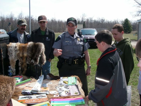 Michigan Conservation Officer Andrea Erratt talks to kids at a Charlevoix Rod and Gun Club Youth Day event.